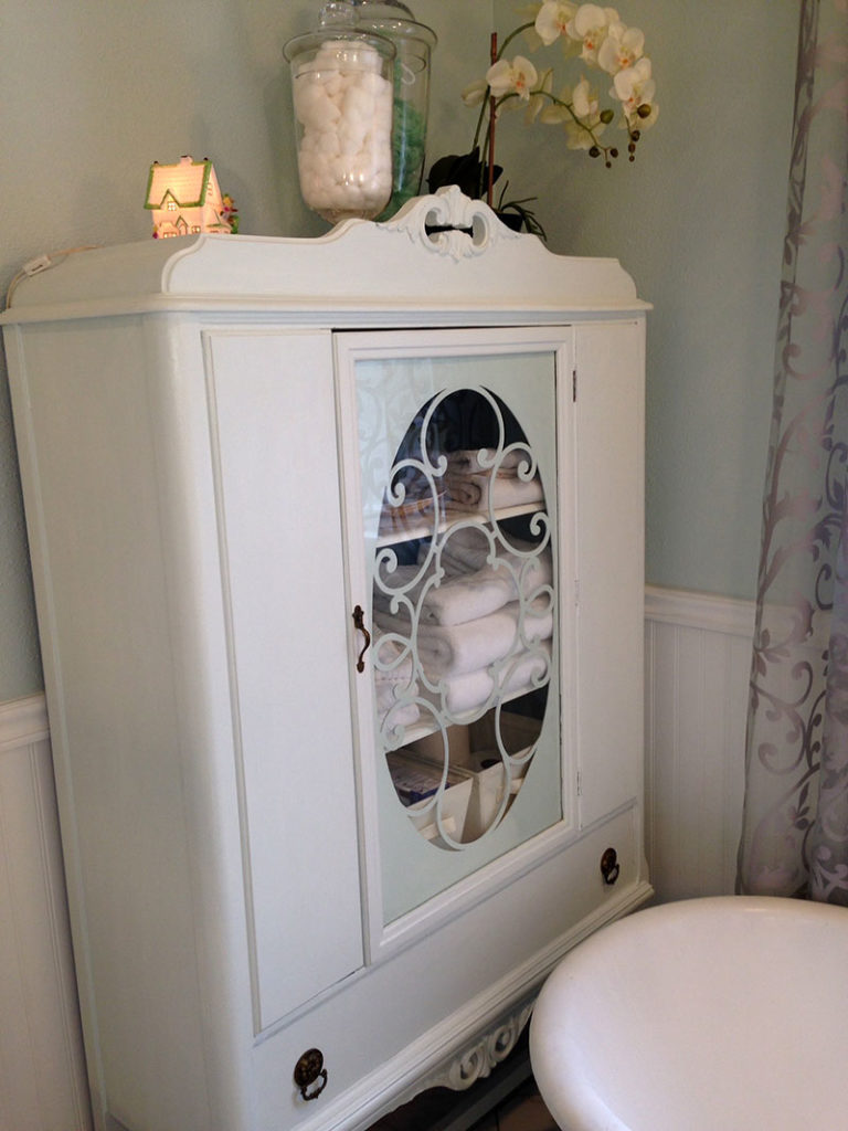 An antique china cabinet of the same era as the sideboard/vanity (and the house) now serves as bathroom storage. We went to Sacramento to get this piece, which I re-painted. See the little cottage night light I bought on Etsy?